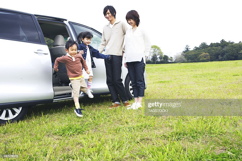 Family getting off a car in prairie : Stock Photo