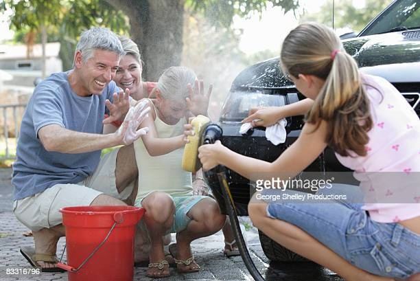 family getting sprayed washing a car - wet t shirt girls stock photos and pictures