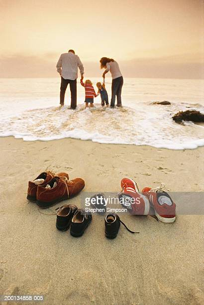 Family getting their feet wet in ocean, rear view
