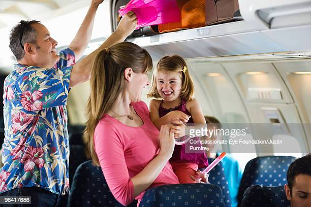 family getting to their seats on an airplane