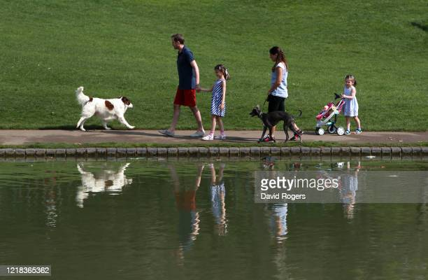 Family go for a walk in Abington Park on April 12, 2020 in Northampton, United Kingdom. Public Easter events have been cancelled across the country,...
