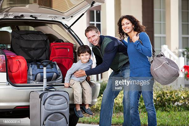 Family going on road trip with suitcases in car