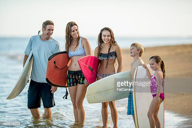 Family Going Surfing On Vacation Stock Photo