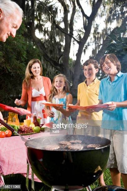Family grilling burgers in back yard