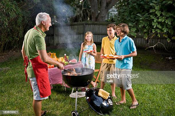 Family grilling burgers on backyard barbecue grill
