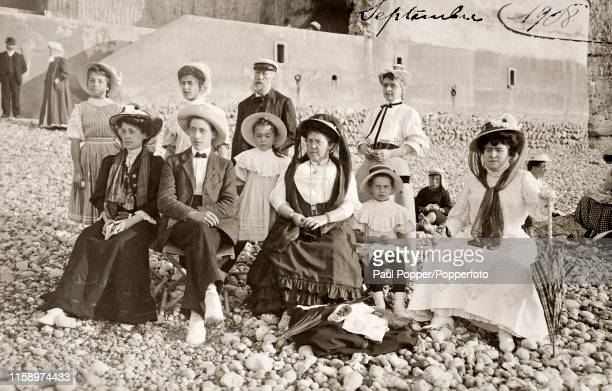 Family group in their Sunday best on a stony beach in France, circa September 1908.