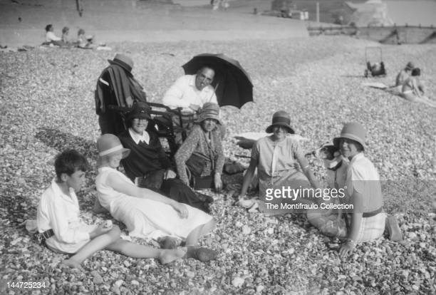 A family group of man women and boy sitting on a pebbled beach all the women are wearing cloche hats and one is holding a pet dog with people and...