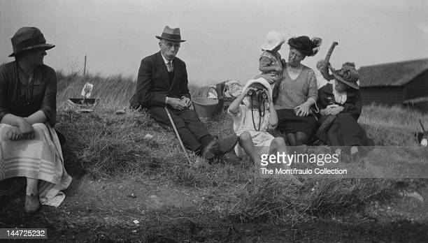 Family group of men, women and children sitting on a grassy mound on a sandy English beach, one of the children is peering through a pair of...