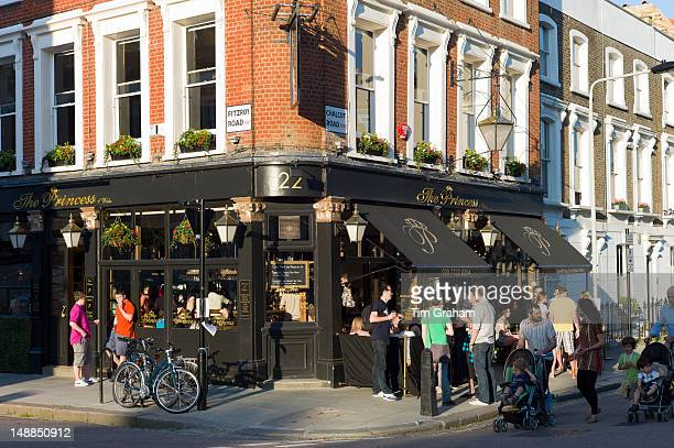 Family group passing customers enjoying warm weather at The Princess traditional London pub in Chalcot Road Primrose Hill London