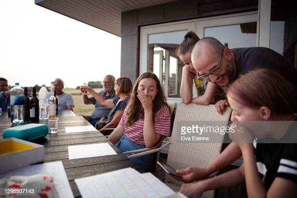 family group sat at an outdoor dining table with an adult showing shocked teenagers something funny on a mobile phone - denmark stock pictures, royalty-free photos & images