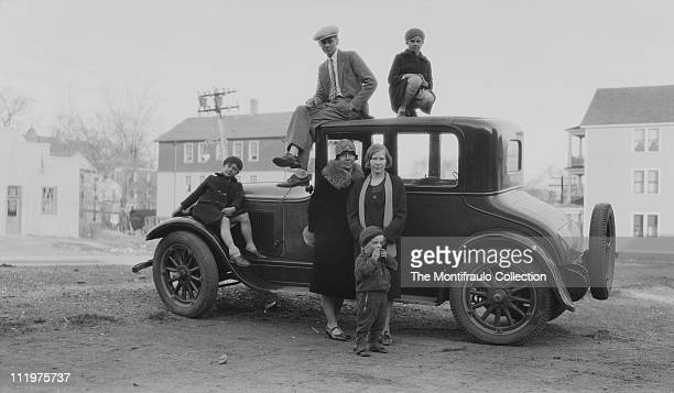 A family group shot of three children two women and a cigarette smoking man gathered around and standing on top of a car roof parked on an wide...