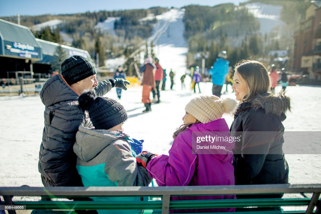 family hacing fun on a bench by the ski slopes at a winter resort