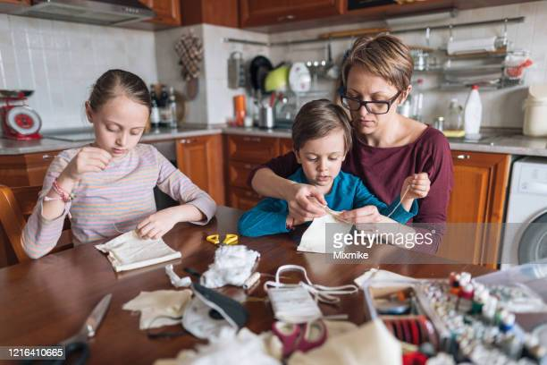 family hand sewing protective face masks - homemade stock pictures, royalty-free photos & images