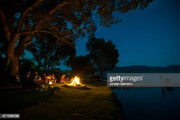 family hanging out around a campfire by a lake - lagerfeuer stock-fotos und bilder
