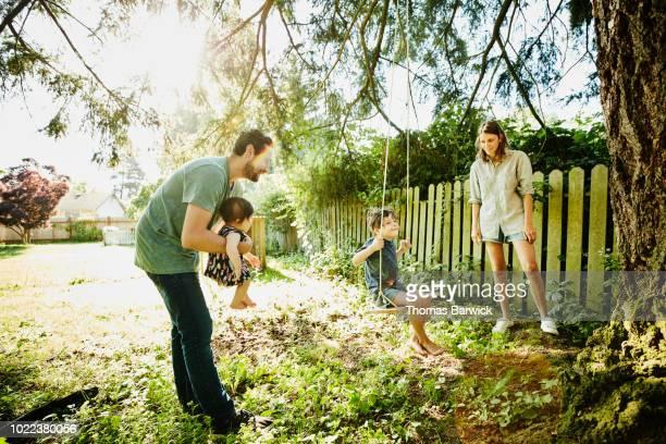 family hanging out together at swing in backyard on summer morning - schommelen bungelen stockfoto's en -beelden
