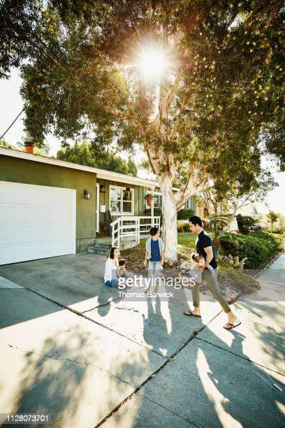 Family hanging out together in front yard on summer morning