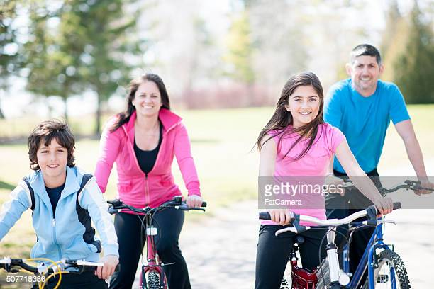 Family Happily Biking Outside on a Sunny Day