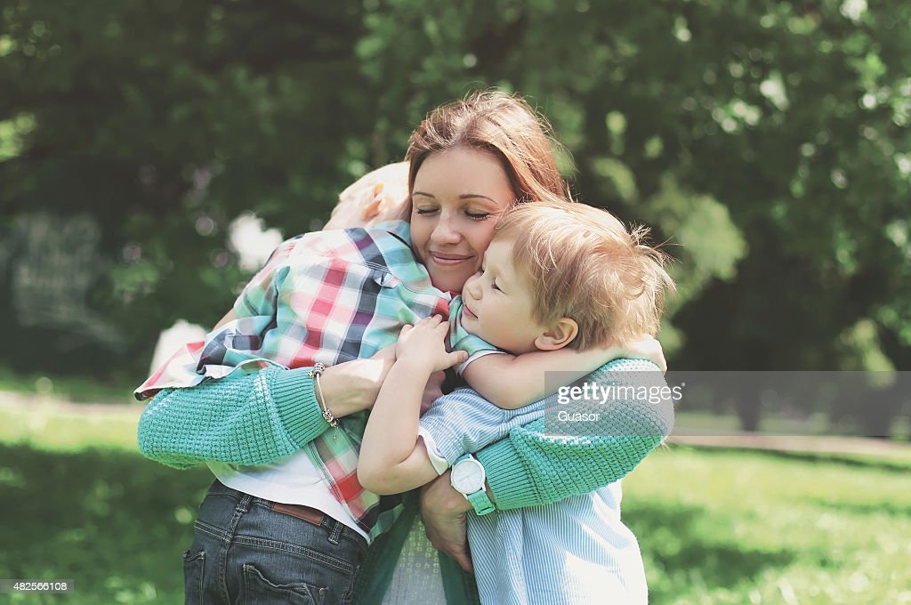 Family happiness! Happy mother tenderly embracing his two sons i : Stock Photo