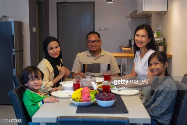 family hari raya aidilfitri dinner together,  break fasting with friend of other ethnic - fasting activity stock pictures, royalty-free photos & images