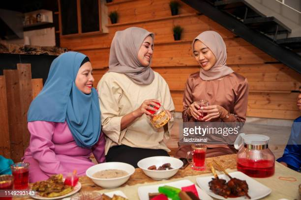 a family hari raya aidilfitri / eid-ul-fitr meal and celebration in malaysia - hari raya celebration stock pictures, royalty-free photos & images