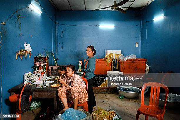 A family has breakfast in their shop front in a wet market on November 26 2013 in Siem Reap Cambodia Cambodian continues their daily life despite a...