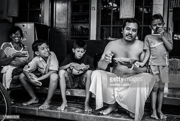 Family has lunch in the shade of their family compound situated off one of the quite alleyways in Legian, Bali, Indonesia 2012.