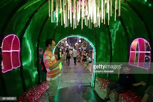Family have fun inside a photo kiosk along Orchard Road on November 23 2013 in Singapore Attracting thousands of tourists every year the famous...