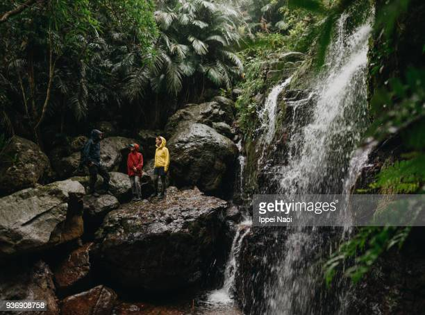 Family having a break during hiking by jungle waterfall in the rain