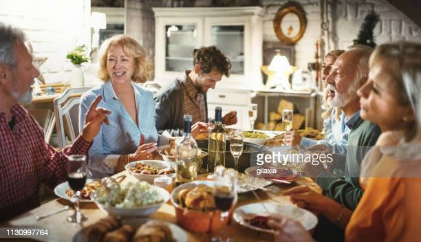 family having a dinner party. - dinner table stock photos and pictures