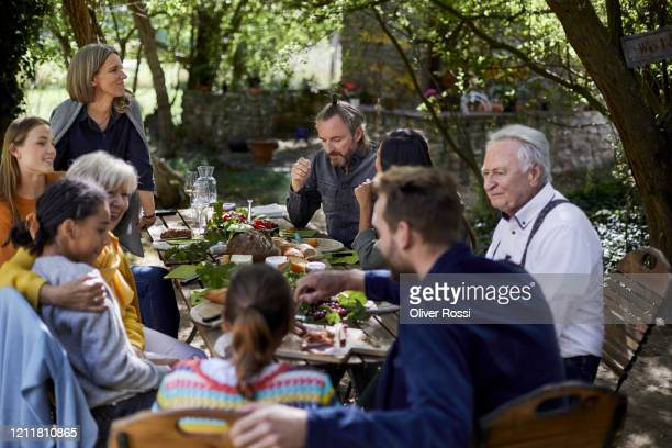 family having a garden party dining al fresco - déjeuner photos et images de collection