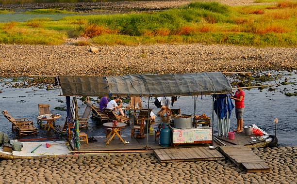 Family Having A Picnic From Raft With Furniture In The Li River At - Picnic table raft