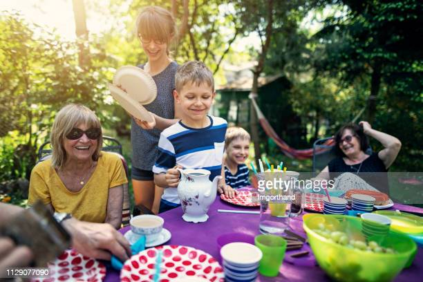 family having barbecue in the garden - plastic plate stock photos and pictures