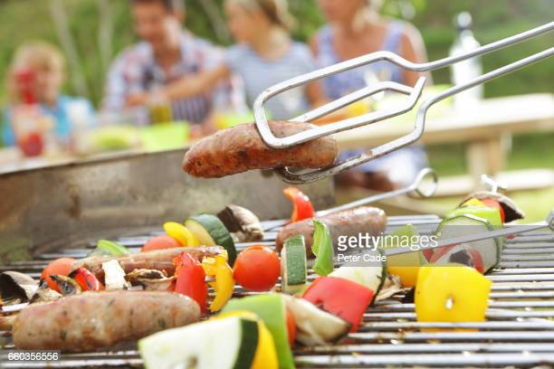 family having bbq in garden, close up of food - sausage stock pictures, royalty-free photos & images