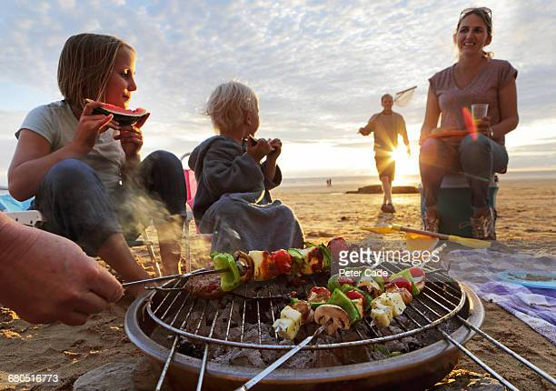 Family having BBQ on beach at sunset