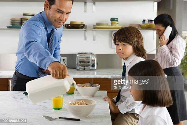 Family having breakfast, father pouring milk over cereal