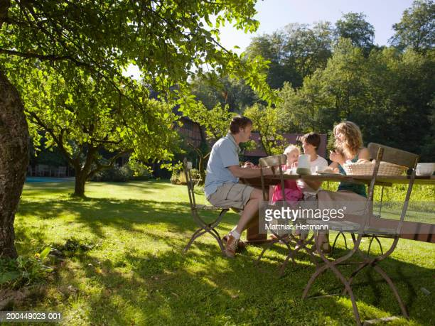 Family having breakfast in garden with daughter (3-5) smiling