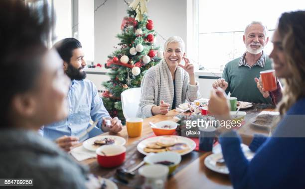 family having breakfast on christmas morning. - mid adult men stock pictures, royalty-free photos & images