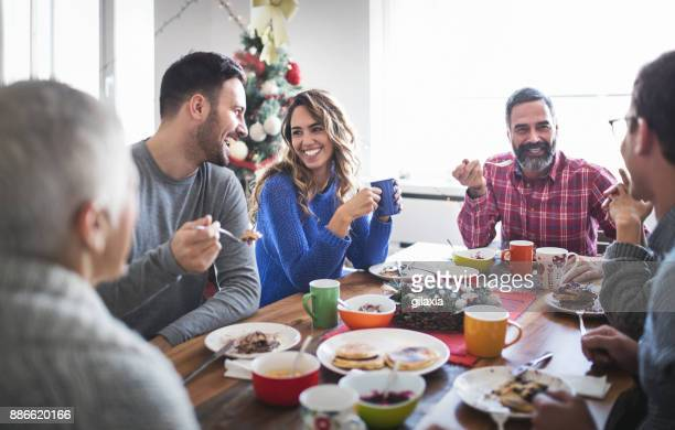 family having breakfast on christmas morning. - christmas dinner stock photos and pictures