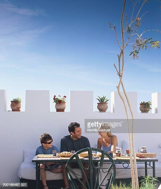 Family having breakfast on roof terrace, smiling