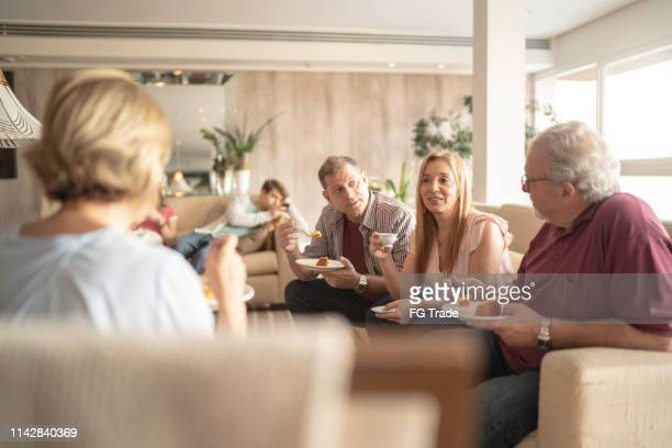 family having coffee and cake together at living room - large family stock pictures, royalty-free photos & images