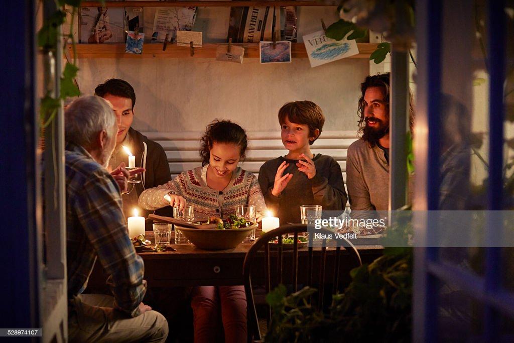 Family having cozy dinner en garden house : Stock Photo