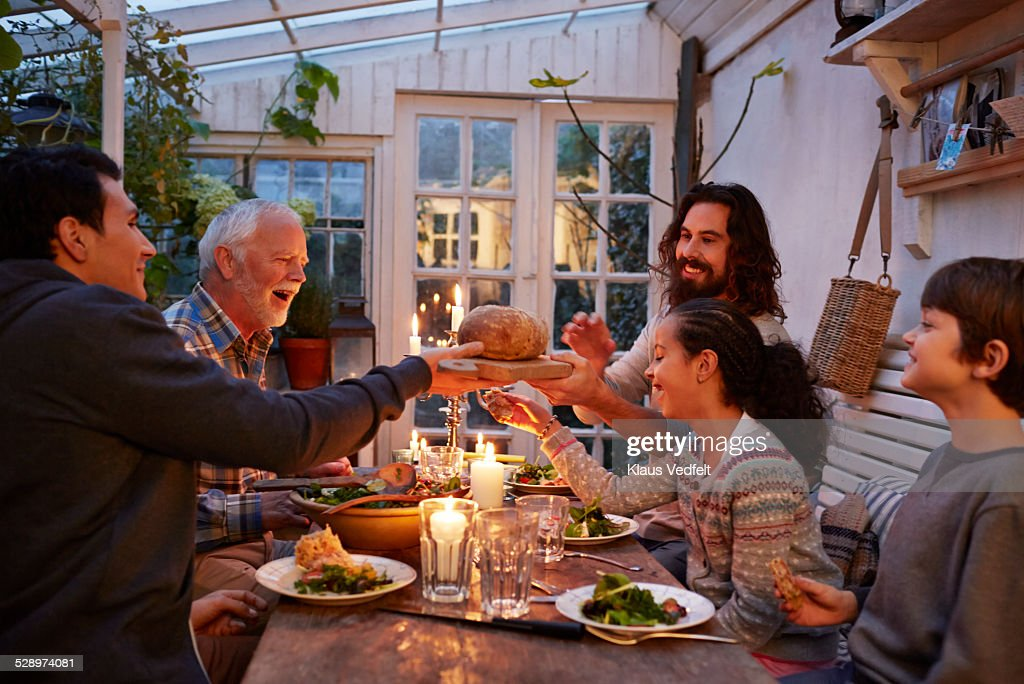 Family having dinner in greenhouse, passing bread : Stock Photo