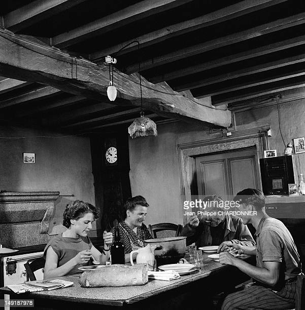 A family having dinner in the dining room of the farm circa 1954 in France