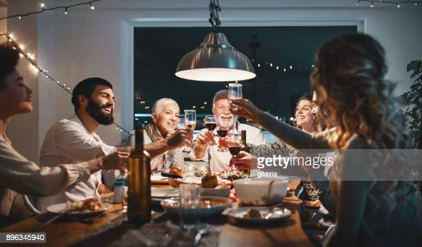 family having dinner on christmas eve. - christmas party stock photos and pictures