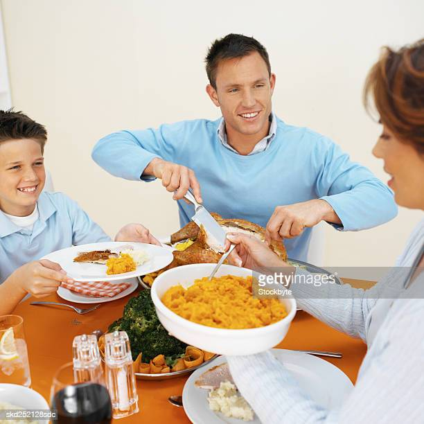 family having dinner together - carving knife stock pictures, royalty-free photos & images