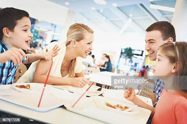 family having enjoyable lunch at a restaurant. - shopping centre stock photos and pictures