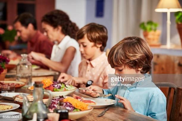 Gezin dat voedsel aan tafel in de eetkamer