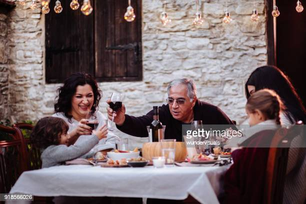 Family having fun and toasting with drinks at dining table