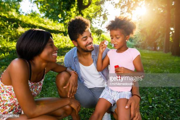 Family having fun blowing soap bubbles in park