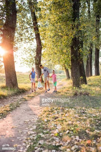 Familie plezier in een park met hun kinderen. Herfst, gele bladeren op het traject.